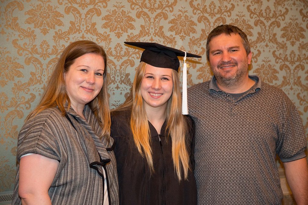 UT High School graduate in cap and gown smiles with her parents
