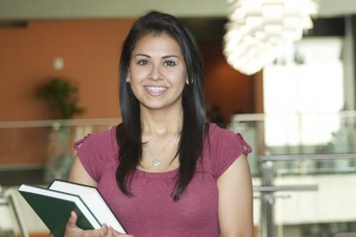 High school student carries her books in the Student Activities Center building